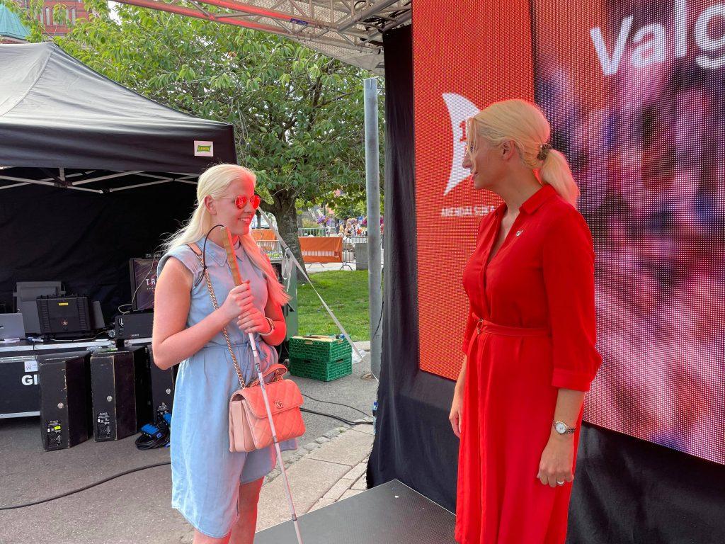 Silje står ved siden av politiker Mirell Høyer-Berntsen fra SV. De ser på hverandre og prater sammen.
