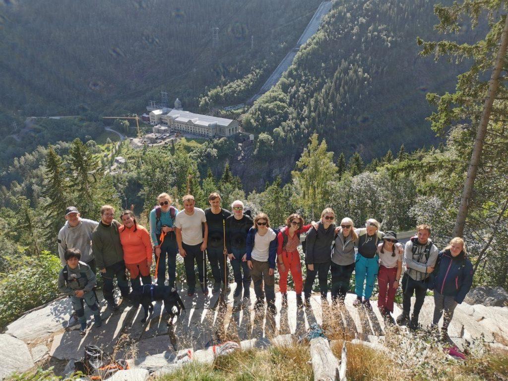 På bildet ser vi alle som var med på turen til Gaustatoppen stå på toppen av et fjell, de smiler til kameraet. I bakgrunnen ser vi skog og en bygning.
