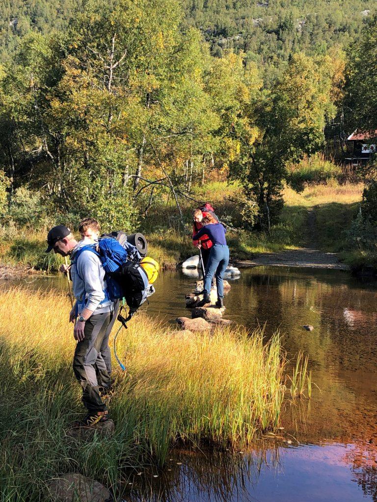 På bildet ser vi to deltakere og to fellesledsagere krysse en elv. De hjelper hverandre over.