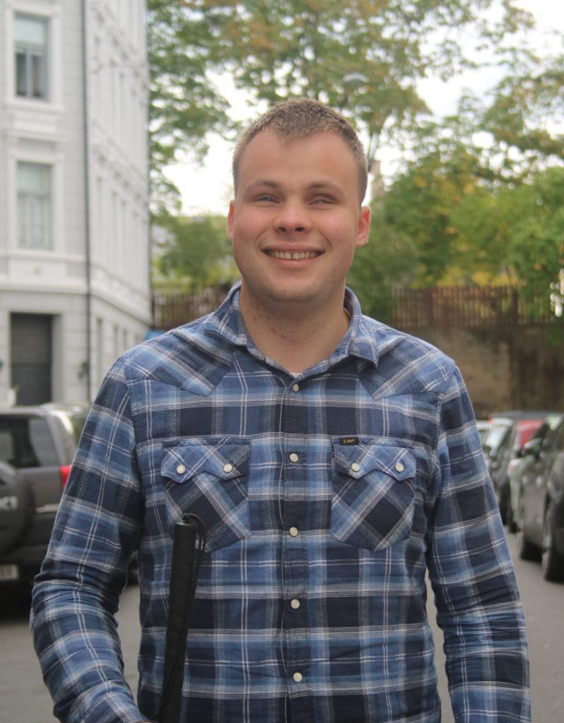 Bildet er av Henning Knudsen. Henning ser i kameraet og smiler. Henning har kort brunt hår, i bakgrunnen ser vi flere biler og noen trær. Henning har på seg en blå rutete skjorte.