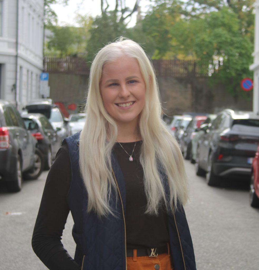 Bildet er av Silje Solvang. Silje ser i kameraet og smiler. Hun har langt blondt hår og i bakgrunnen ser vi flere biler og noen trær. Silje har på seg en svart jakke og oransje skjørt.