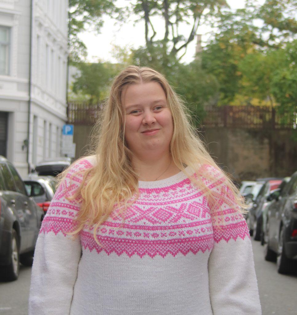 Bildet er av Tina Sleire Sandvik. Tina ser i kameraet og smiler. Hun har langt blondt hår og i bakgrunnen ser vi flere biler og noen trær. Tina har på seg en strikkegenser i hvit med rosa mønster over brystet.