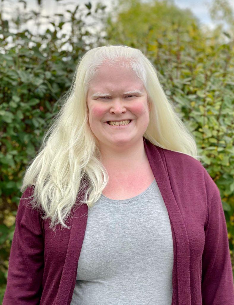 Bildet er av Katrin Kvæl Hasselberg. Katrin ser i kameraet og smiler stort. Katrin har langt blondt hår, og i bakgrunnen ser vi en stor grønn busk. Katrin har på seg grå t-skjorte og en mørk lilla cardigan.