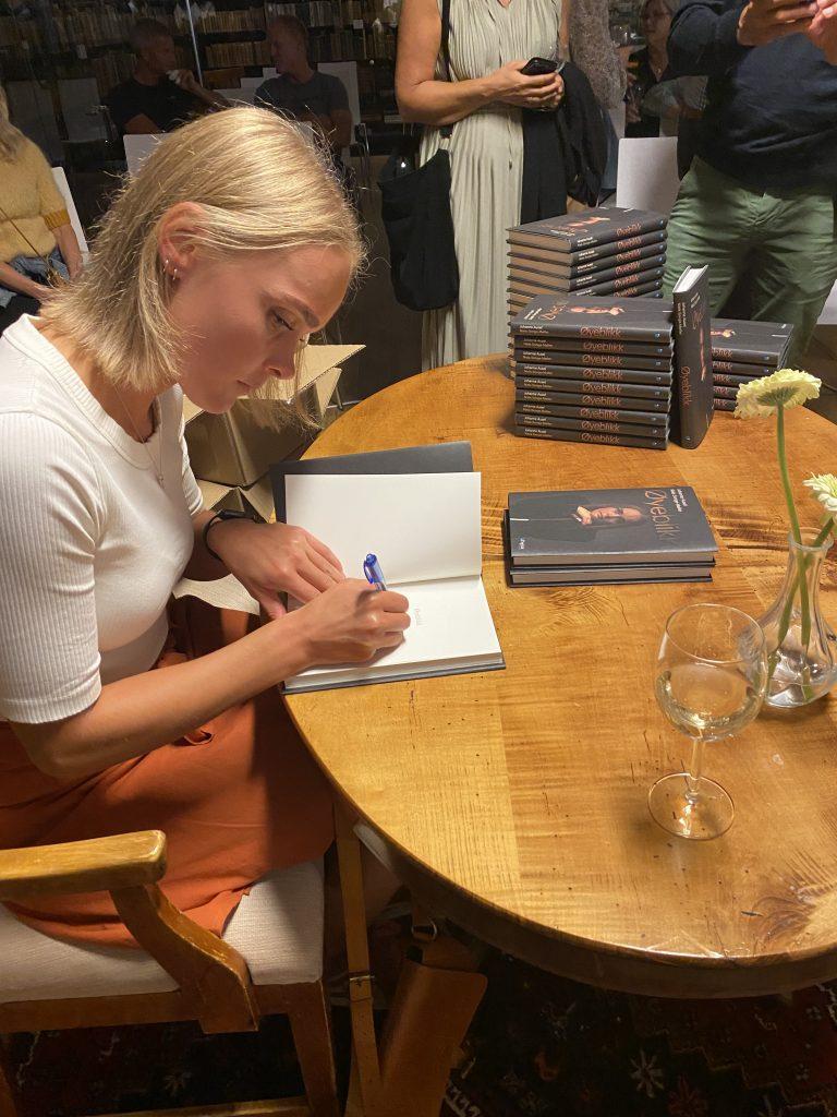 """På bildet sitter Johanne ved et bord og signerer første siden av boken sin. På bordet ligger det mange eksemplarer av boka """"øyeblikk"""" klare for å bli signert. Johanne ser konsentrert ut og har på seg en hvit t-skjorte og et brunt skjørt."""